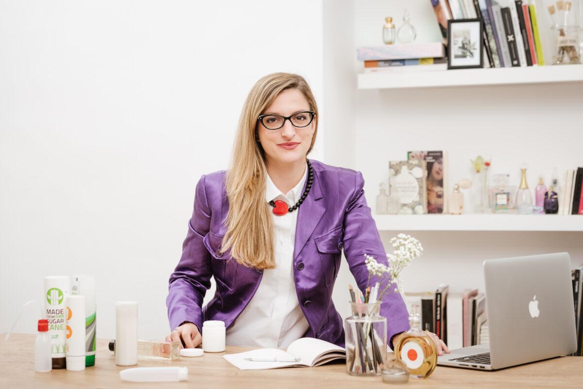 Eleonora Gavino Project Manager settore cosmetico alla scrivania con confezioni di cosmetici e pc